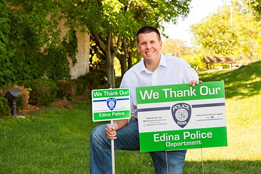 Greg Daggett kneeling and holding his We Thank Our Edina Police Department signs
