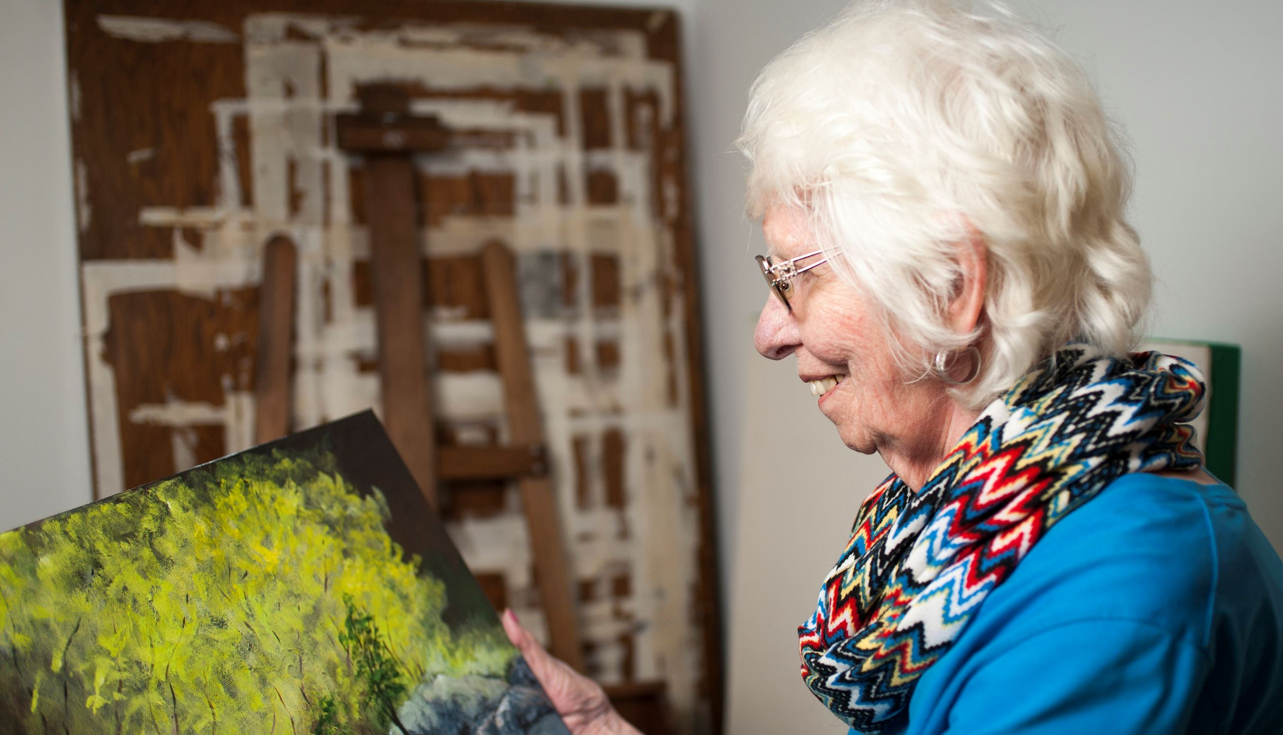 Marian Alstad looking at a painting in her hands