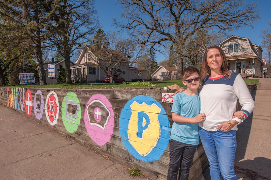 Heather and Alex Lane stand next to Thank U mural outside their home
